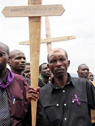 Disaster survivors hold crosses with the names of the 1994 genocide victims marching in the streets of Kigali 4-2006